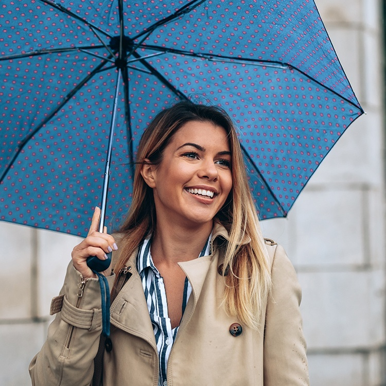 Woman with dental insurance smiling and holding an umbrella