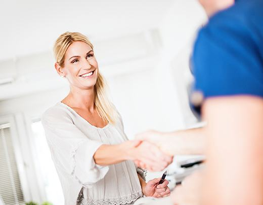 Woman shaking hands with dental team member as she completes dental insurance forms