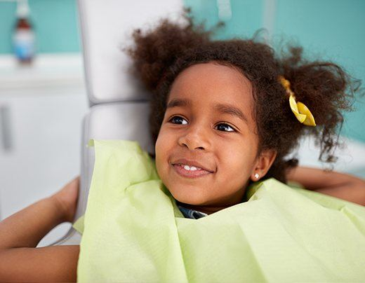 Little girl smiling at first dental checkup