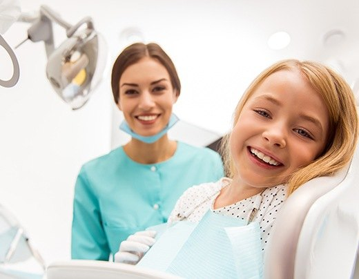 Young girl laughing during dental checkup