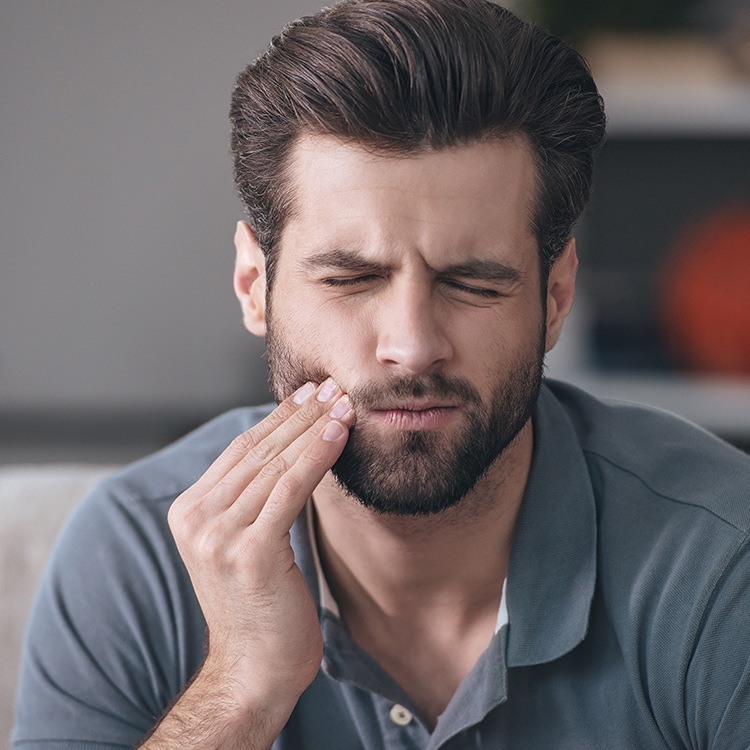 Man holding cheek before tooth extraction