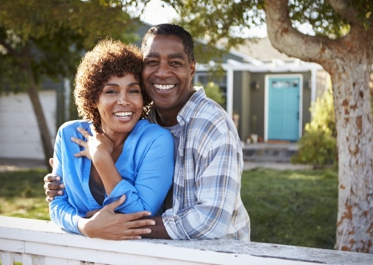 Man and woman with dental insurance smiling outdoors