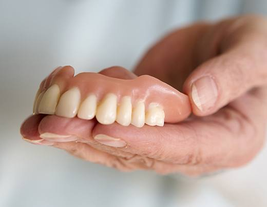 Hand holding a full set of dentures