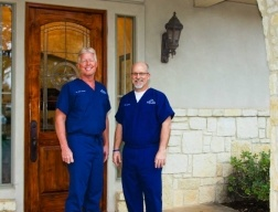 Boerne Texas dentists smiling by dental office entrance