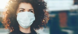 High-risk woman in mask follows recommendations by her Boerne, TX dentist