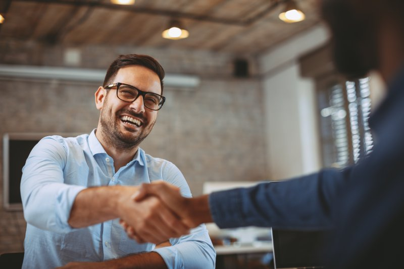 Man smiling and shaking hands at job interview
